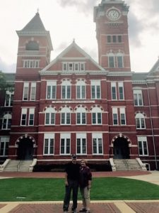 Samford Hall with 2 old grads in front.