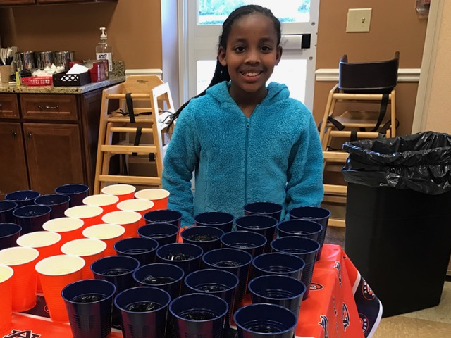 Matt's daughter Birti happily serving drinks at the orange and blue table.