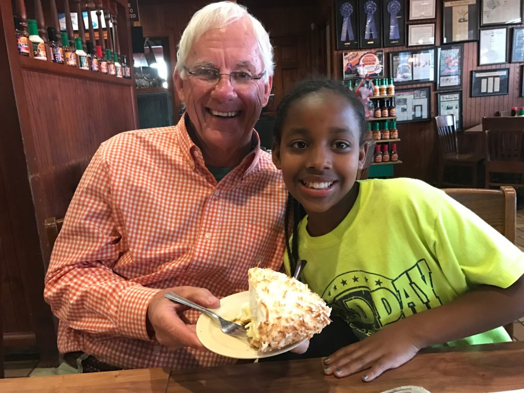 A granddaddy and granddaughter get ready to share a piece of pie. I wonder who ate the most?