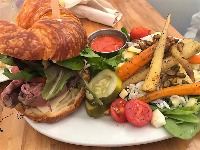 Roast beef on a croissant with a veggie salad featuring pickled carrots